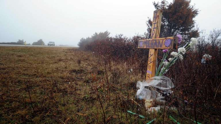 A car passes by a makeshift memorial for