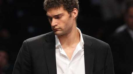 Injured Brook Lopez looks on during a game