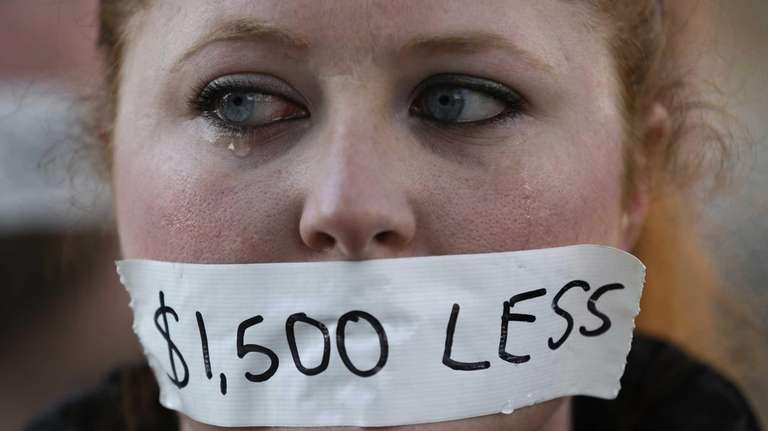 A silent protester cries while wearing a sticker