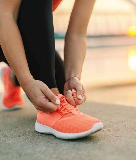 Close up of sporty woman tying shoelace while