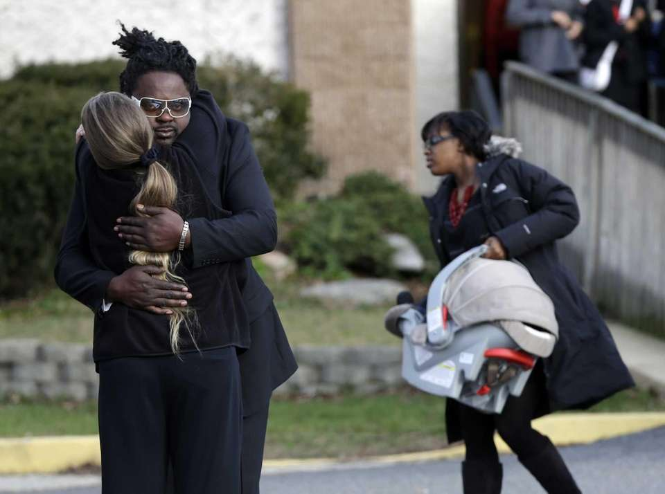 Mourners hug after leaving the church where Jovan