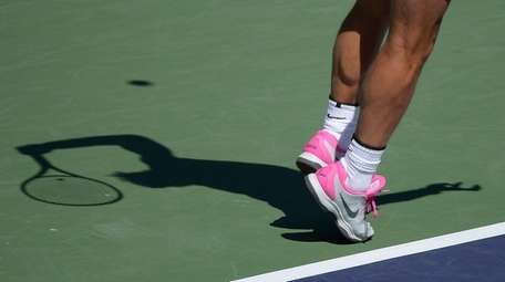 Rafael Nadal casts a shadow as he serves