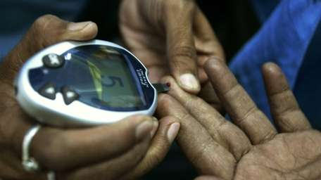A health worker takes a blood sample from