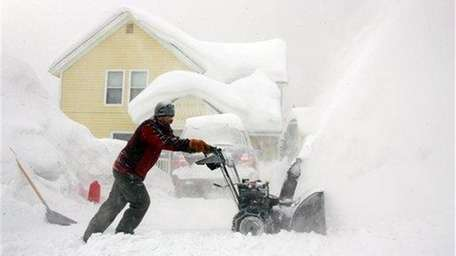 A man uses his snow-blower to remove the