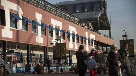 Tourists and shoppers visit Pier 17 at the