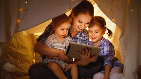 Mother and children playing games on a tablet.
