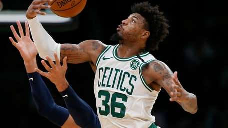 The Celtics' Marcus Smart gathers in a rebound