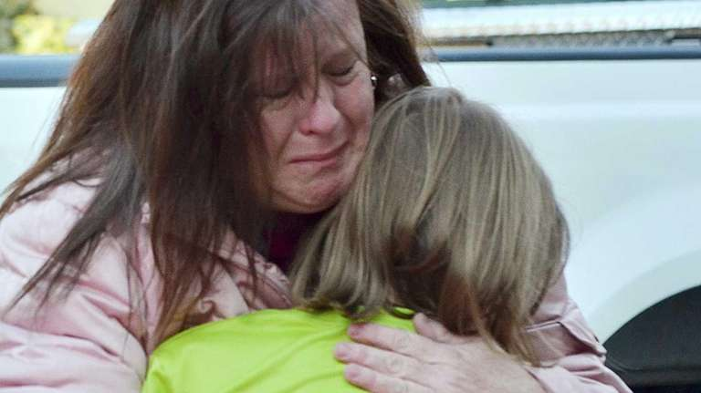 A mother hugs her daughter following a shooting