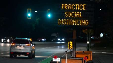 """A sign reminding people about """"social distancing"""" in"""