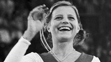 USSR's Olga Korbut holds up her gold medal