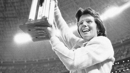 Billie Jean King holds the winner's trophy high
