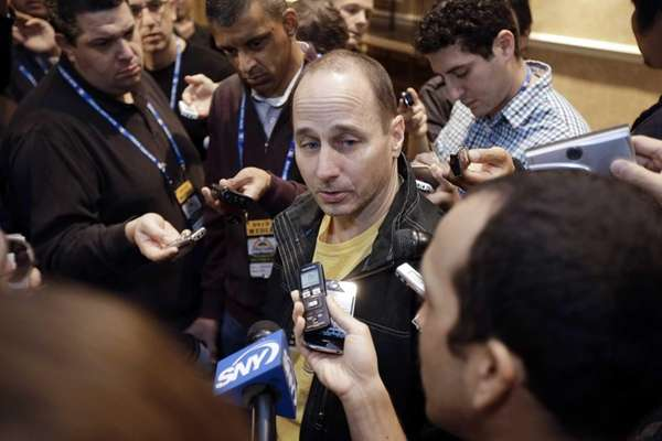 Brian Cashman talks with reporters during the Rule