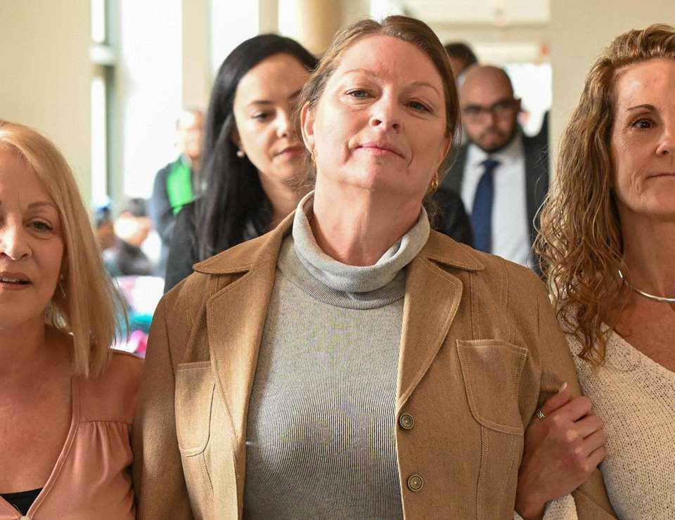 Ann Marie Drago, center, leaves courtroom at First