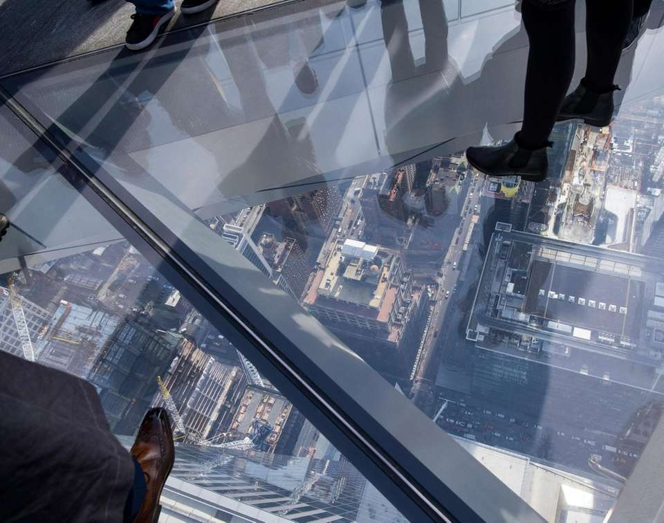 Visitors stand on the glass floor panels, some