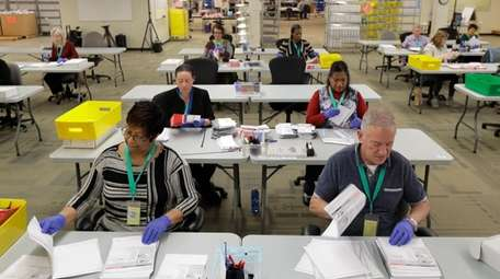 Workers handle ballots from the Washington state primary