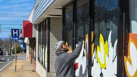 Ben Silberstein paints the windows of a business