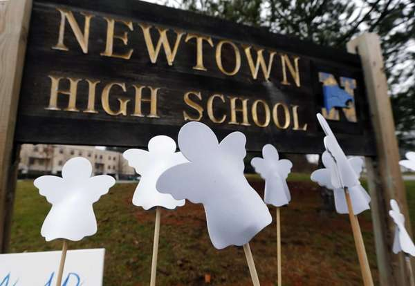 Angel cutouts are displayed outside Newtown High School
