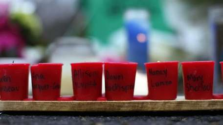 Candles with the names of shooting victims written