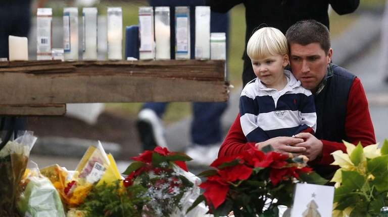 A man holds a child while paying respects