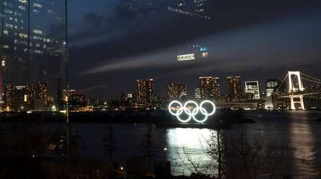 The Olympic rings are reflected in the glass