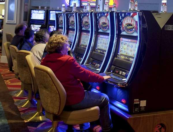 Guests play slot machines at the Resorts World