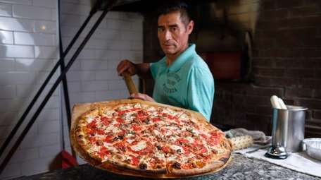 Pizzaiolo Luis Barrera holds a large sausage pizza