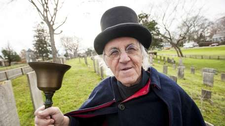 East Hampton Town crier Hugh King stands in