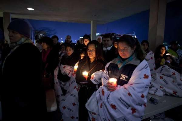 Residents hold a candlelight vigil outside Newtown High
