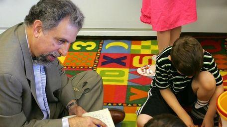 Alan Finder interviews children at a school in