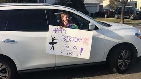 Lauren Gilmore holds a sign for classmate Ava