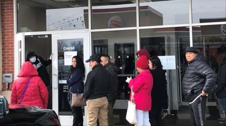 Customers wait on line to be admitted to