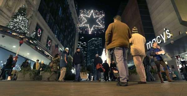 Shoppers walk past holiday decorations at the Downtown