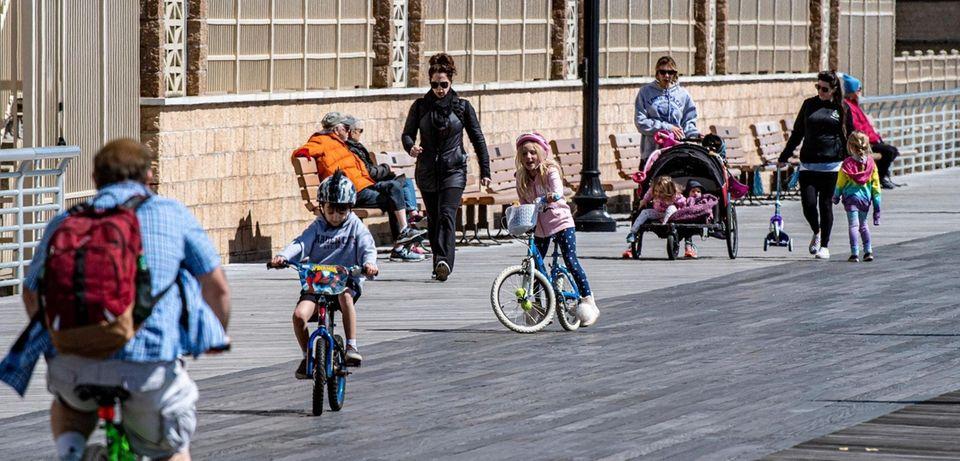 People walk and ride bikes along the boardwalk