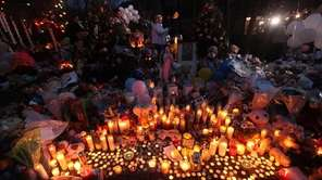 Candles are lit among mementos at a memorial