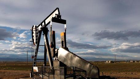 An oil pump jack in a field adjacent