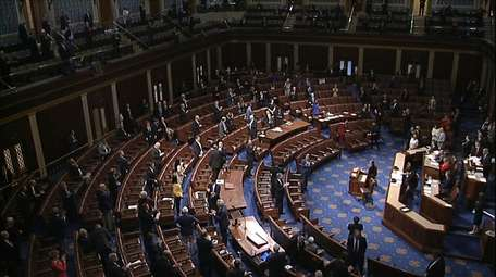 Members of the House stand after they passed