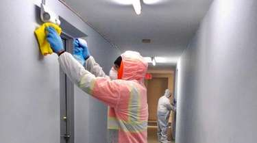 Workers from Greenlion Cleaning disinfect an office for