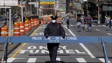 A police officer stands at a crosswalk on