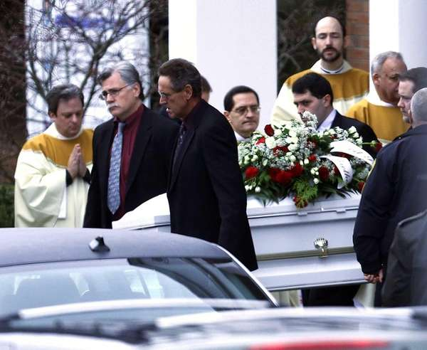 Pallbearers carry a casket out of St. Rose