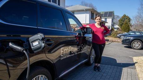 Tara McDermott with her electric Mitsubishi car at
