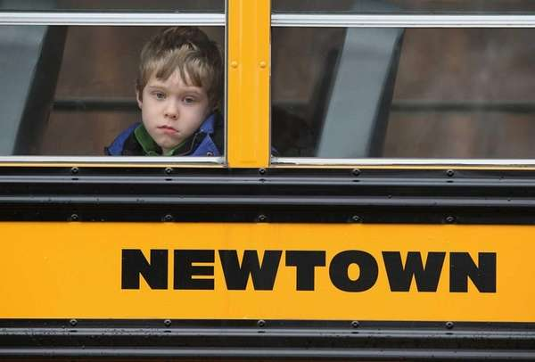 A child gazes from a school bus as