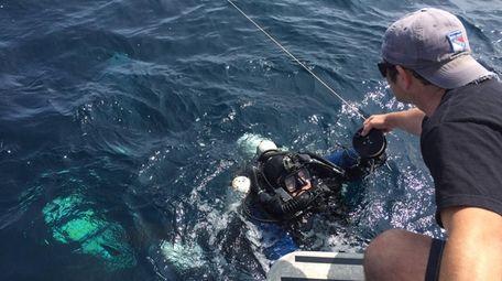 John Bricker hands up dive equipment to Jim