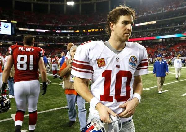 Eli Manning walks off the field after a