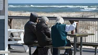 Three women sit at Ponquogue Beach in Hampton