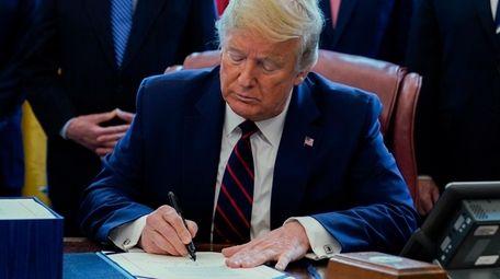 President Donald Trump signs the $2.2 trillion coronavirus