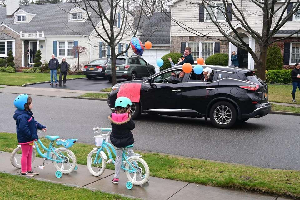 People participate in a drive by parade in