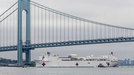 The Navy hospital ship USNS Comfort passes under