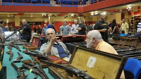 An assortment of rifles line tables at a