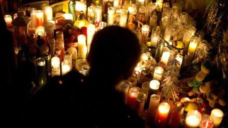 Candles line a sidewalk memorial in honor of