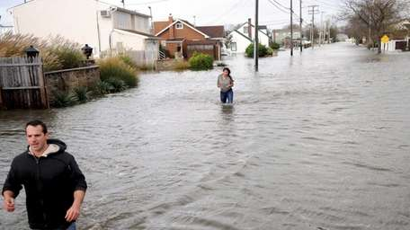 Residents try to flee through waist-deep waters on